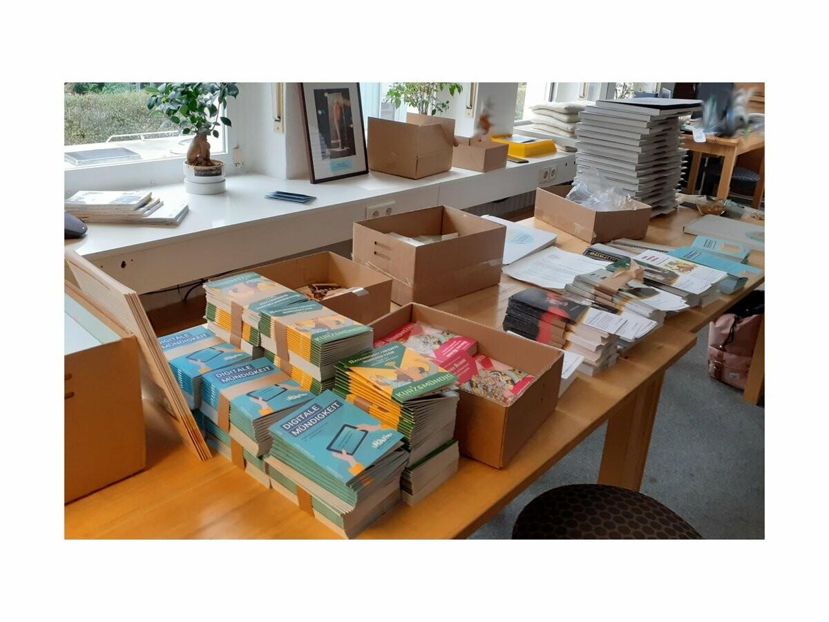ein langer Tisch mit Stapeln von Broschüren der Kurz-und-Mündig-Reihe und Faltblättern von Digitalcourage